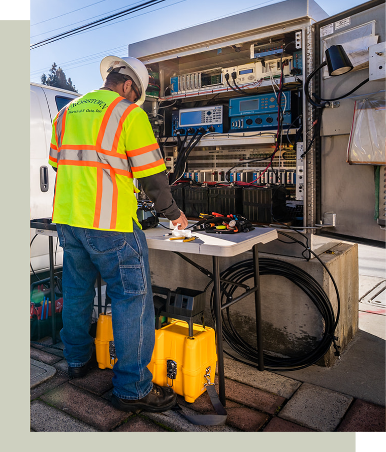 Electrical Contractor in front of equipment